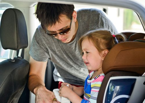 Dad Strapping His Daughter Into The Car